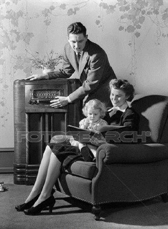 1940S Family Of 3 Listening To Radio While Mother Reads Book.