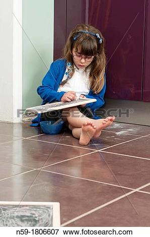 Picture of Five year old girl in school uniform writing on a small.