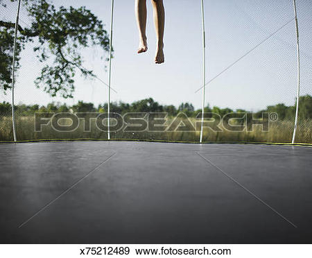 Stock Photograph of 9 Year old girl jumping on a wet trampoline.