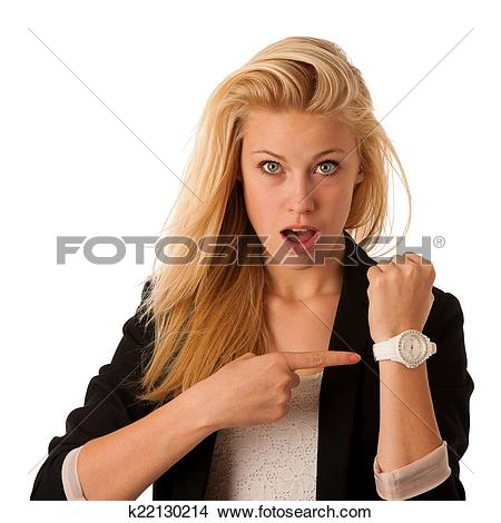 Stock Photo of Young blonde woman looks at her watch when she is.