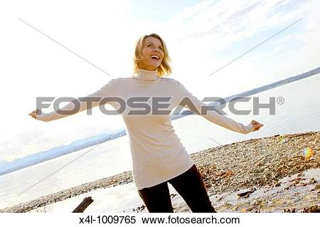 Stock Image of blonde woman in the late fall at a lake x4l.