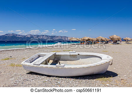 White small rowboat boat dry docked on the beach.
