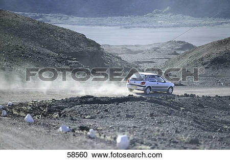 Stock Photography of Car traveling on a road leaving behind a.