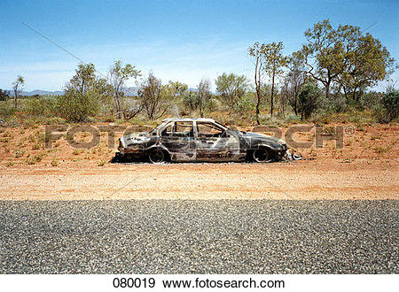 Stock Photograph of An abandoned car on the side of a desert road.