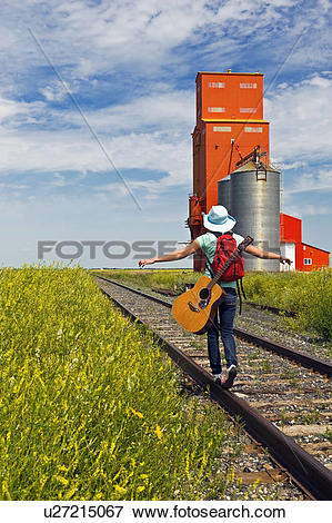 Picture of 18 year old girl carrying guitar walking along railway.
