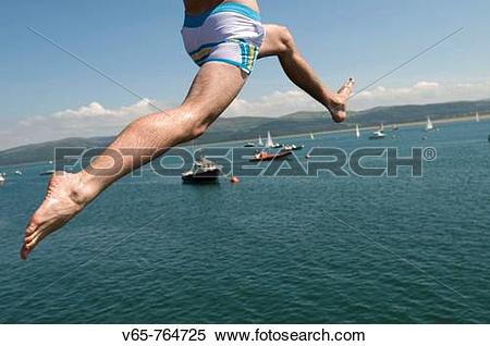 Stock Image of Close up of the legs of a man leaping off the jetty.