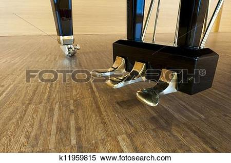 Stock Image of golden piano pedals of a concert grand piano.