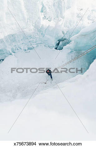 Stock Photo of Abseiler at bottom of snow covered mountain.