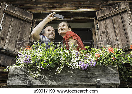 Stock Photography of Couple taking self portrait from chalet.