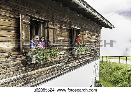 Stock Photo of Portrait of family at chalet windows, Achenkirch.