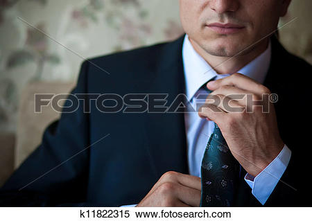 Stock Image of businessman in suit adjusts his tie k11822315.