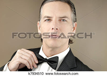 Stock Photography of Confident Gentleman In Tux Adjusts BowTIe.