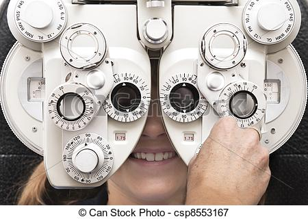 Picture of an optometrist adjusts the dials on the phoropter.