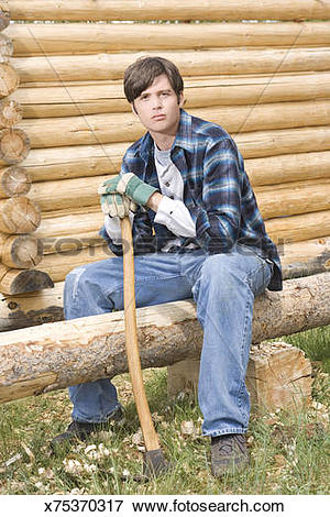 Picture of Man sitting on log with adze x75370317.