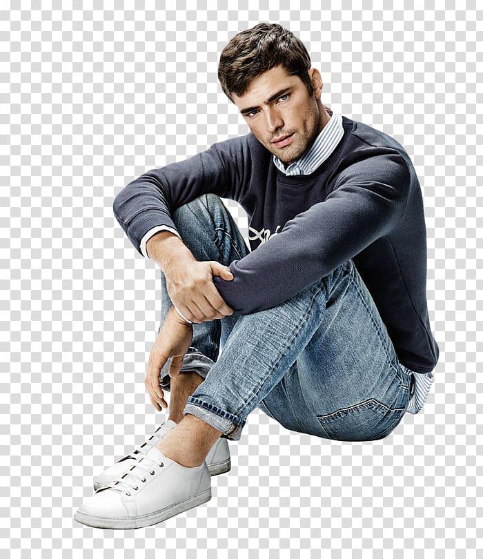 Male Model s, man in black sweatshirt and blue jeans sitting.