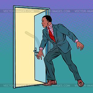 African man opens door.