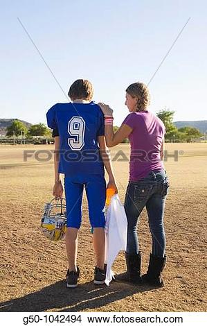 Stock Photo of Girl comforting boy after football game loss g50.