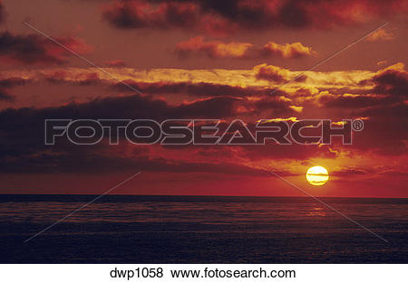 Pictures of Sunset over the ocean. The large yellow sun gives an.