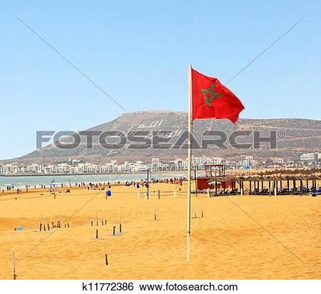 Stock Images of The beautiful beach in Agadir with flag of Morocco.