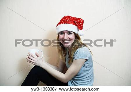 Picture of pretty girl in the Christmas hat against light wall.