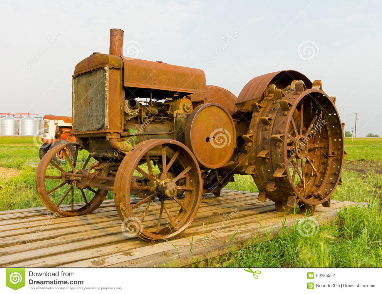 An Antique Tractor With Spiked Iron Wheels At An Agricultural.