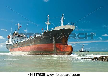 Stock Images of Cargo ship run aground on rocky shore k16147536.