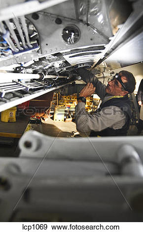 Stock Photograph of mechanic installing an aileron control cable.