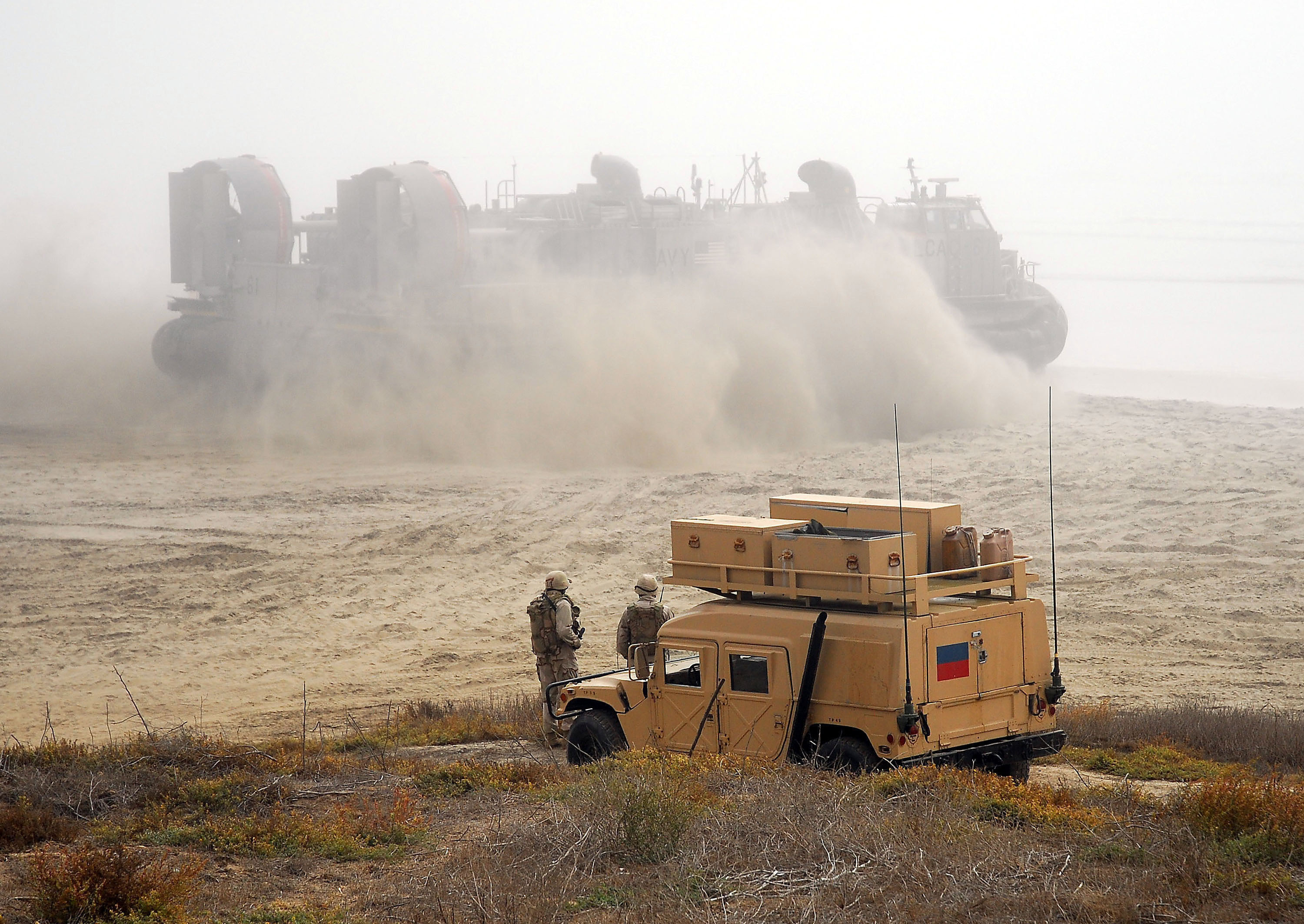 Stock Photo: Marines on Grass Watch a Landing Craft Air Cushion on.
