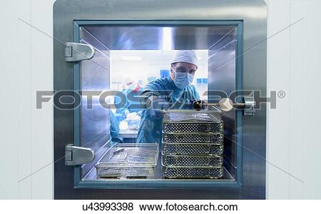 Pictures of Worker putting surgical instruments into air lock in.