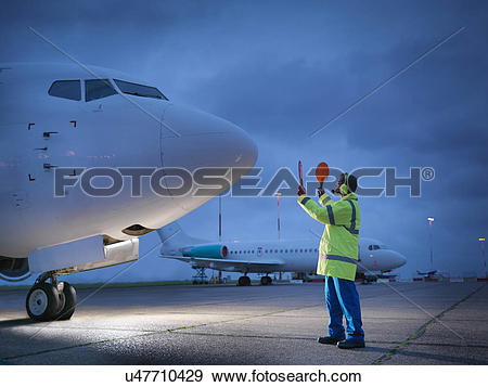 Stock Photograph of Airport worker guiding aircraft on runway at.