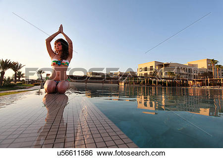 Stock Images of Woman practicing yoga poolside, Aqaba, Tala Bay.