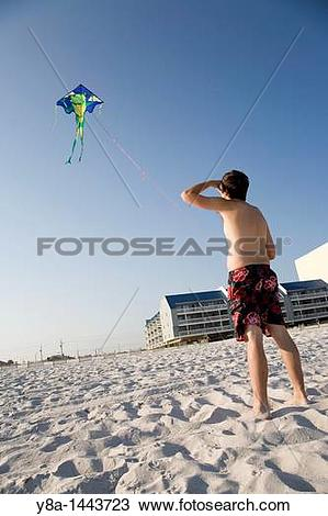Stock Photo of Man flying a kite at the beach in Gulf Shores.