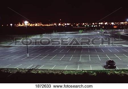 Stock Photo of an almost empty parking lot illuminated at night.
