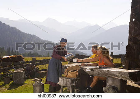 Picture of Couple taking break at alpine hut, peasant woman.