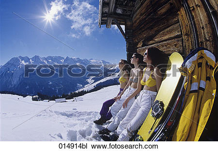 Stock Photo of three young women in bikini tops sunbathing outside.