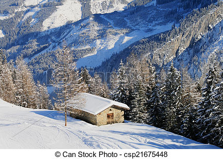 Stock Photo of Alpine hut in winter with roofs covered with a.