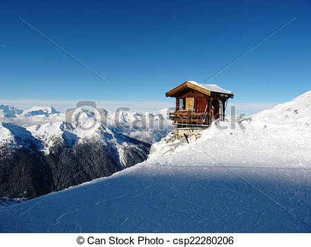 Stock Photography of A mountain hut on the side of a snow covered.