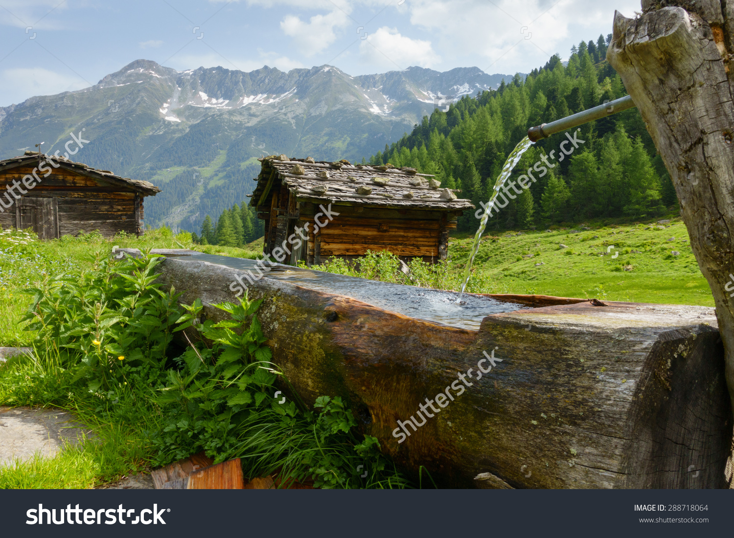 Old Mountain Huts In The Alps And Wooden Fountain Stock Photo.