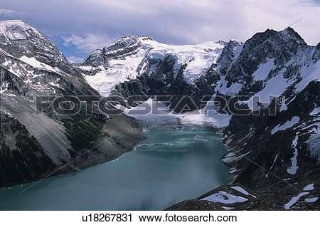 Stock Photography of Alpine lake with glacier and mountains.