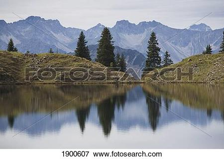 Picture of alpine lake reflecting a mountain range and trees.