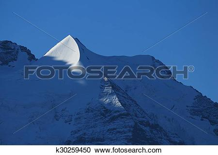 Stock Photography of Pointed mountain Peak next to Mt Jungfrau.