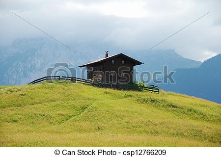 Stock Photography of Brown cabin on hill in Alps.