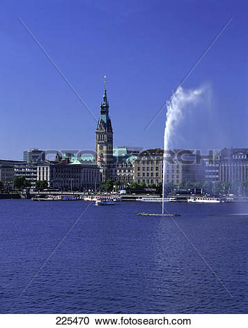 Stock Photography of Fountain in lake against buildings in city.