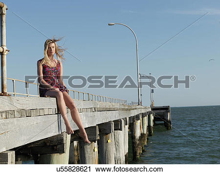 "Stock Photography of ""Young woman sitting on breezy pier, Altona."