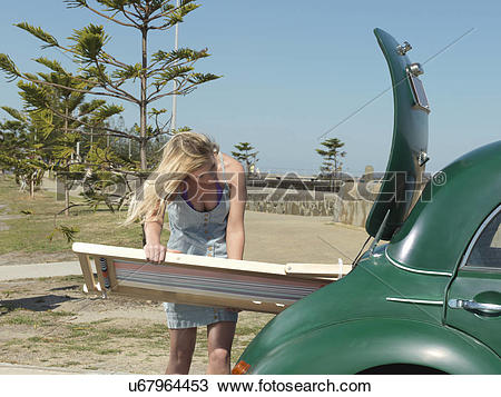 "Stock Photo of ""Young woman removing deck chair from car boot at."