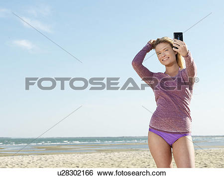 "Stock Images of ""Young woman on beach posing for smartphone selfie."