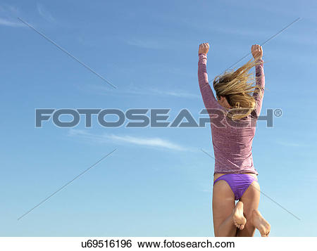 "Stock Images of ""Rear view of young woman jumping mid air, Altona."