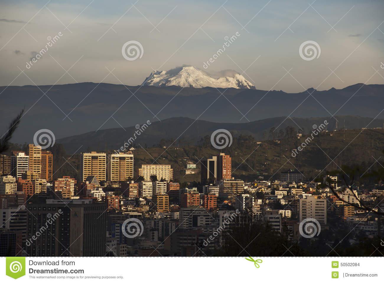 Quito At Sunset With Antisana Volcano Stock Photo.