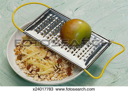Stock Photo of Vegetable grater with apple above muesli x24017783.