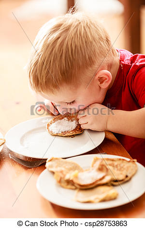 Stock Image of Little boy eating apple pancakes at home.